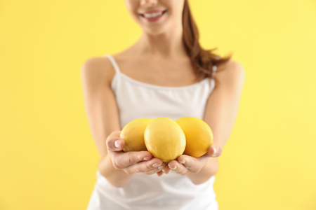 Beautiful young woman with ripe lemons on color background