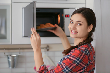 Frau stellt Teller mit Gebäck in der Mikrowelle drinnen Standard-Bild