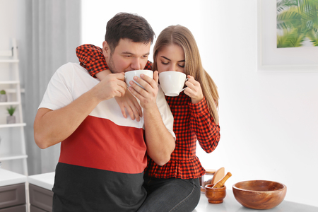 Cute young lovely couple drinking tea at home