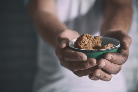 Poor man holding bowl with bread, closeup