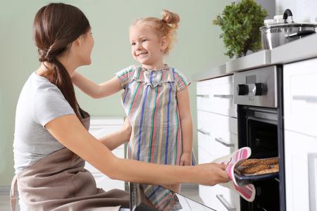 Little girl watching her mother bake cookies in oven indoors