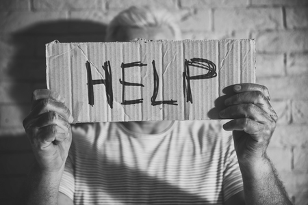 Poor man holding sign with word HELP on brick wall background. Black and white effect