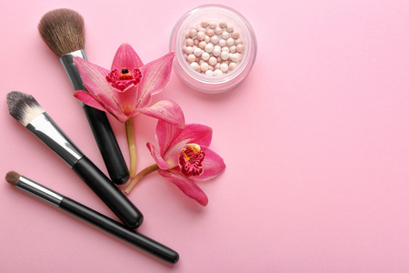 Brushes with decorative cosmetic of professional makeup artist and flowers on color background