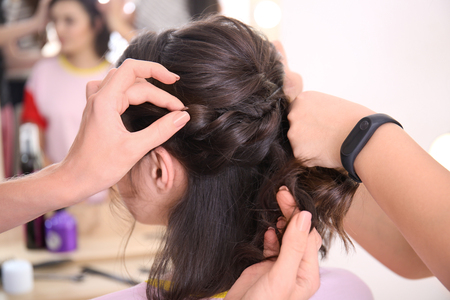Professioneller Friseur und Auszubildender, der mit Kunden im Salon arbeitet. Ausbildungskonzept