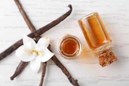 Bouteilles en verre avec extrait de vanille sur table en bois, vue de dessus Banque d'images