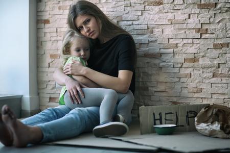 Bezdomna biedna kobieta z córeczką siedzącą przy ceglanym murze i proszącą o pomoc Zdjęcie Seryjne