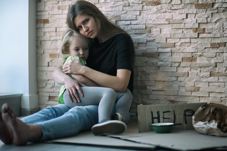Homeless poor woman and her little daughter sitting near brick wall and asking for help Stockfoto