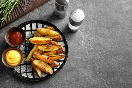 Plate with tasty potato wedges and sauces on table