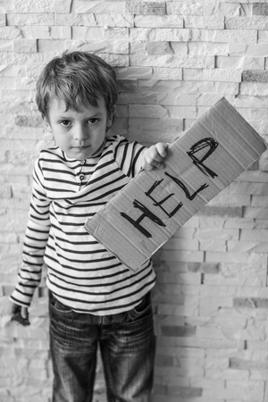 Homeless poor boy holding carton board with word HELP near brick wall Foto de archivo