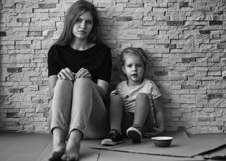 Homeless poor woman with little daughter sitting near brick wall