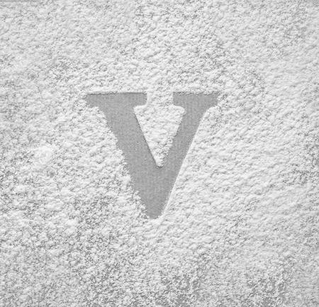 Silhouette of letter V on scattered flour