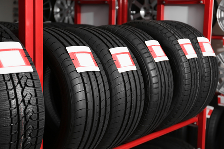 Stand with car tires in automobile store Banco de Imagens