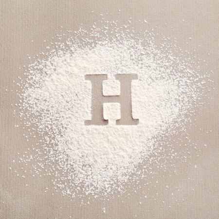 Silhouette of letter H on scattered flour