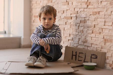 Bezdomny biedny chłopiec z pustą miską i tekturową tablicą ze słowem POMOC siedzący przy ceglanym murze