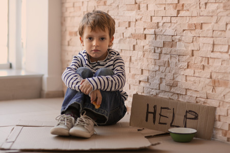 Homeless poor boy with empty bowl and carton board with word HELP sitting near brick wall