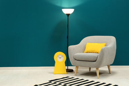 Trendy armchair with lamp near shaded spruce wall 스톡 콘텐츠