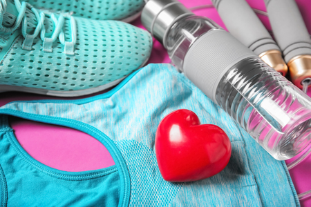 Gym stuff and red heart on color background. Cardio training concept