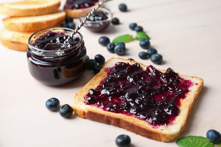 Delicious toast with sweet jam on wooden table