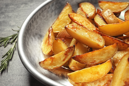 Dish with delicious baked potato wedges, closeup