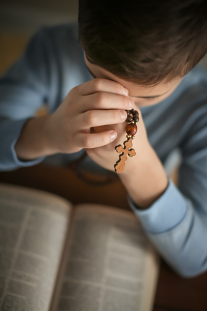 Little boy with cross praying over Bible at table