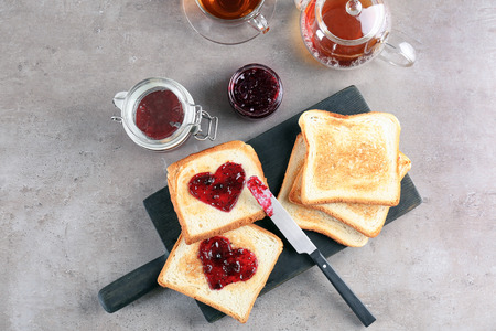 Delicious toasts with sweet jam on wooden board Stock Photo