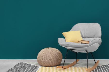 Trendy armchair near shaded spruce wall Imagens