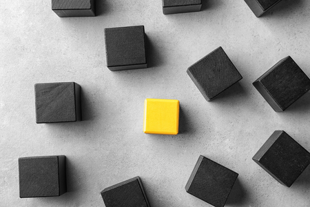 One yellow cube standing out from others on light background. Think different concept 免版税图像