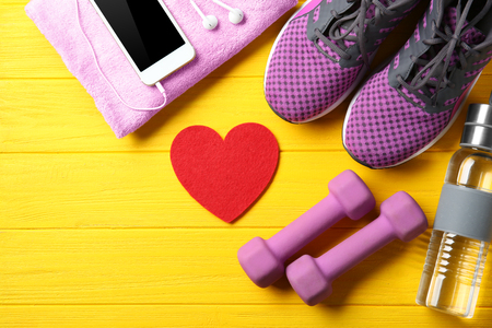 Gym stuff, phone and red heart on color wooden background. Cardio training concept