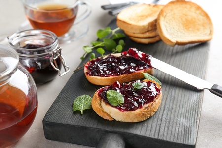 Delicious toasts with sweet jam on wooden board 写真素材
