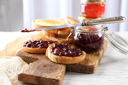 Jar and delicious toasts with sweet jam on wooden board
