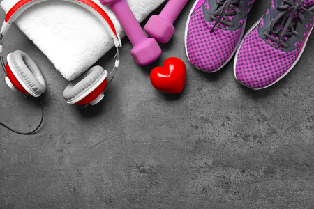 Gym stuff and red heart on grey background. Cardio training concept Imagens
