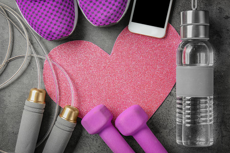 Gym stuff, phone and heart on grey background. Cardio training concept Imagens