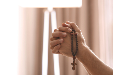 Hands of religious young man with rosary beads praying at home