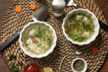 Dishes of delicious soup with dumplings on wicker mat