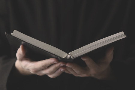 Young priest reading Bible, closeup