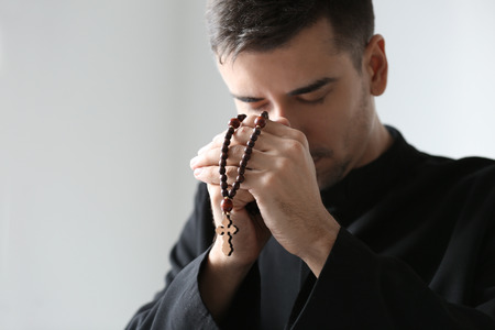 Young priest with rosary beads praying on light background 版權商用圖片 - 112778876
