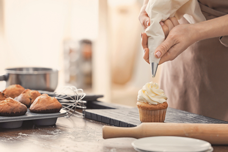 Woman decorating tasty cupcake with cream at table 免版税图像