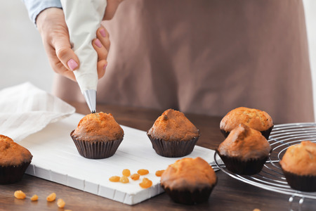 Woman decorating tasty cupcakes with cream at table Standard-Bild