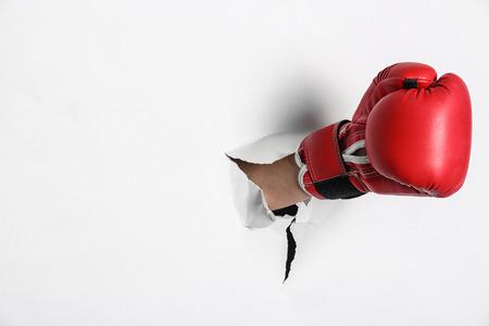Uomo in guantoni da boxe che sfonda carta bianca