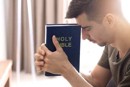 Religious young man with Bible praying at home