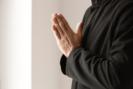 Young priest praying to God indoors Stock Photo