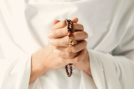 Praying monk with rosary beads, closeup