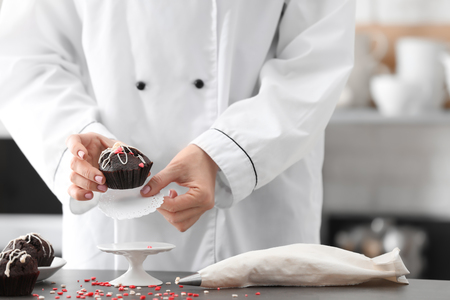 Chef serving tasty cupcake at table