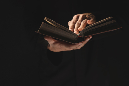 Priest with old Bible on black background, closeup