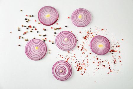 Cut red onion and spices on white background