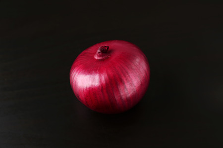 Whole red onion on black background