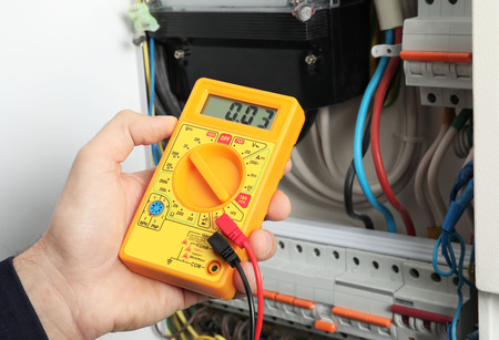 Young electrician measuring voltage in distribution board, closeup
