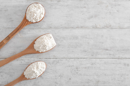 Spoons with flour on wooden background