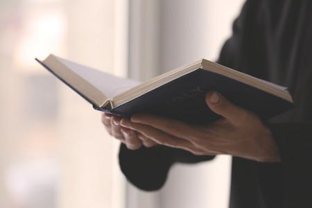 Joven sacerdote leyendo la Biblia en interiores, primer plano