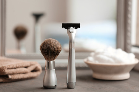 Shaving brush and razor for man on table